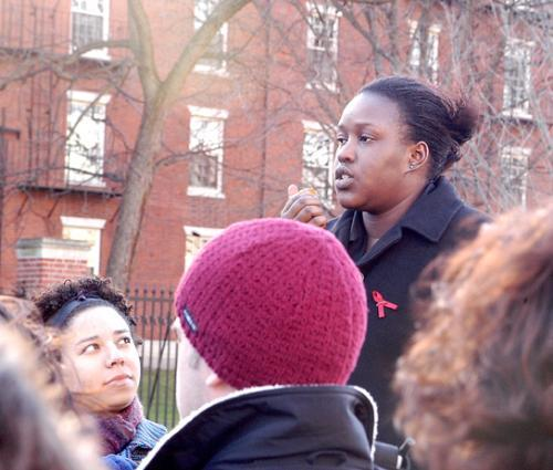 KUDZAI A. MAKOMVA '06 of Zimbabwe speaks of the effects of AIDS in her homeland as AMANDA S. ALEXANDER '04 looks on at a rally outside of the Science Center yesterday.