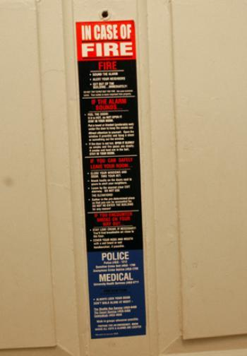 The University advertises SafetyWalk in various venues, including signs on fire doors, like this one in Lowell House...