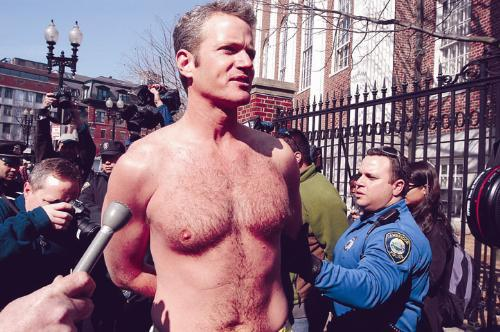 "Dan Mathews, vice president of People for the Ethical Treatment of Animals, is arrested in the Square yesterday with five other protestors, including a Harvard student. Chanting ""Fur out, love in,"" Mathews avoids the media."