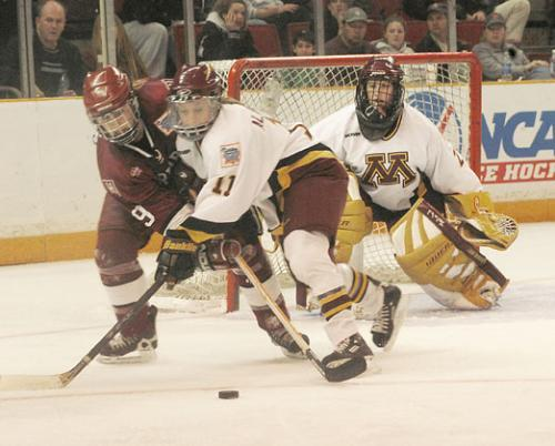 Junior forward Nicole Corriero (9) battles with Minnesota defenseman Ashley Albrecht during last Sunday's NCAA national championship game. Though Corriero and the Crimson fired 33 shots on net, the Golden Gophers shut Harvard down in the third frame.
