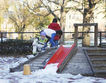 Children play on a playground on Cambridge Common. The city is concerned about dangerous items left in the area by the homeless.