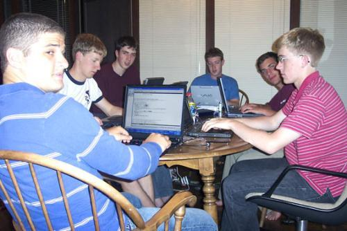 Zuckerberg, back, head of table, and his team of programmers, including Dustin A. Moskovitz '06-'07, left, do their business casually at the kitchen table in Palo Alto, Cal. the summer after founding thefacebook and leaving Harvard.