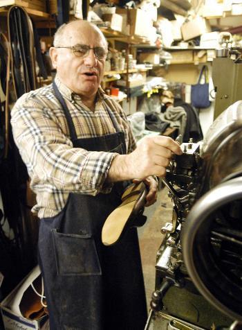 Harvard Square cobbler Christos Soillis works in his shop, Felix's Shoe Repair, yesterday afternoon.