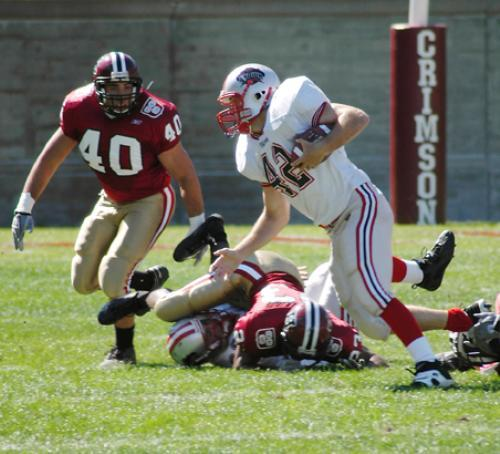 Harvard senior linebacker Matt Thomas swoops in to stop Brown running back Nick Hartigan. The All-American tailback finished with 115 yards on 29 carries, but was kept out of the endzone and under five yards a carry.