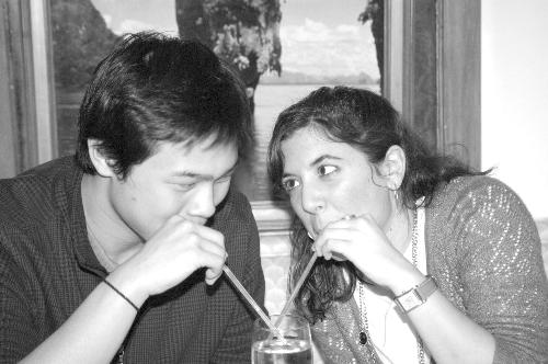 Eric and Christina exercise their lips by sipping from the same drink.