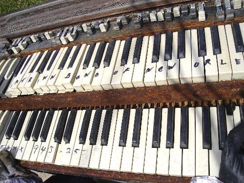 """On this old keyboard are written the words """"Katrina Band of New Orleans."""" The gloves of a toy gorilla play the keys."""