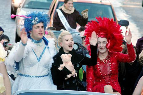 Scarlett Johansson, Hasty Pudding's Woman of the Year, waves alongside two Hasty Pudding Theatricals members in drag costumes during the annual parade down Mass. Ave. Pudding members later roasted the actress.