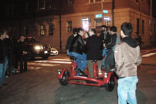 Regina Spektor and members of the Harvard Lampoon ride around Sorrento Square on a 8-seater bike Friday evening as students—many of whom had waited for hours to hear Spektor sing to no avail—look on.