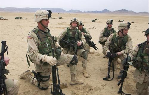 Kevin Kit Parker briefs some soldiers, after they air assaulted into an area on the Afghan-Pakistani border in January 2003. The soldiers are preparing to move in to search a village, while a firefight raged in the mountains above them.