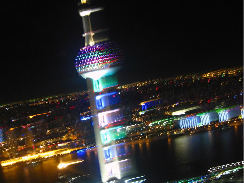 The dizzying view of Shanghai at night, featuring the Oriental Pearl Tower.