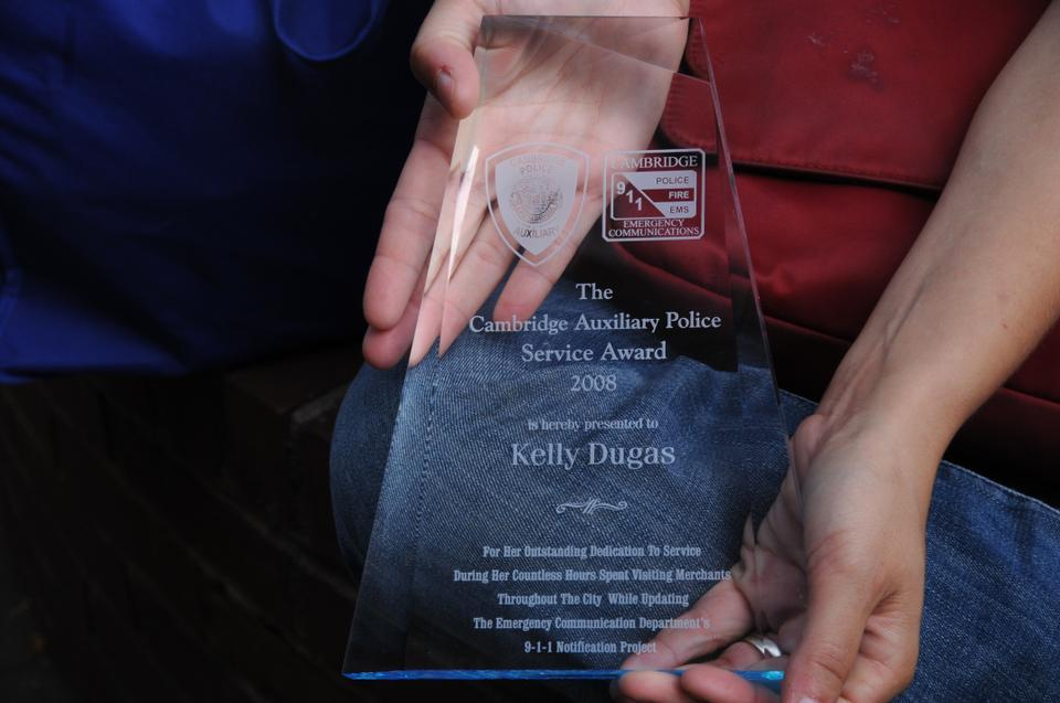 Kelly Dugas Coveney, member of the Chair Club since 2006. shows an award she received from the Cambridge Police Department for collecting emergency callback numbers from city businesses.