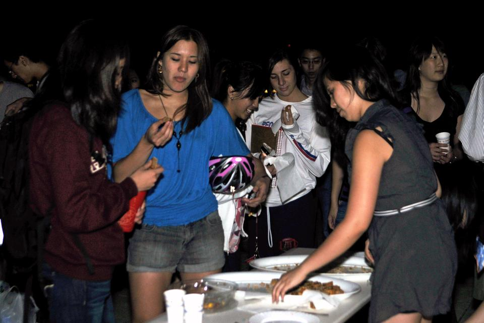 Students enjoy mooncakes and other Chinese pastries while looking at the moon and the Cambridge skyline on the roof of the Science Center at the Mooncake Study break last night.