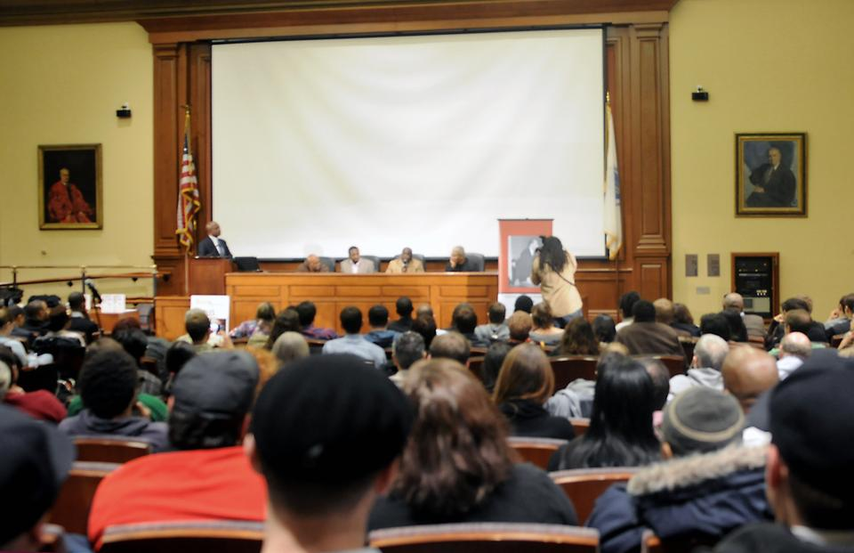 A packed room listens to cast members