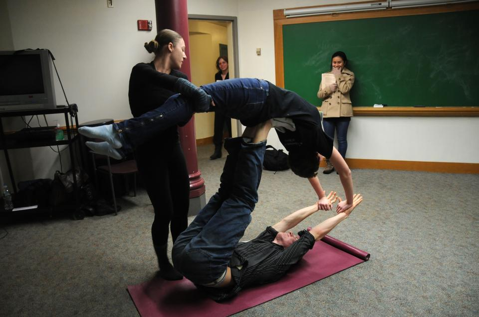 """Sarina M. Patterson '14 (on top), Kobi A. Rex '14 (on bottom), and Marin J. Orlosky-Randow '08 (spotting them) participate in """"A FAAB Affair"""" in the basement of Memorial Hall."""