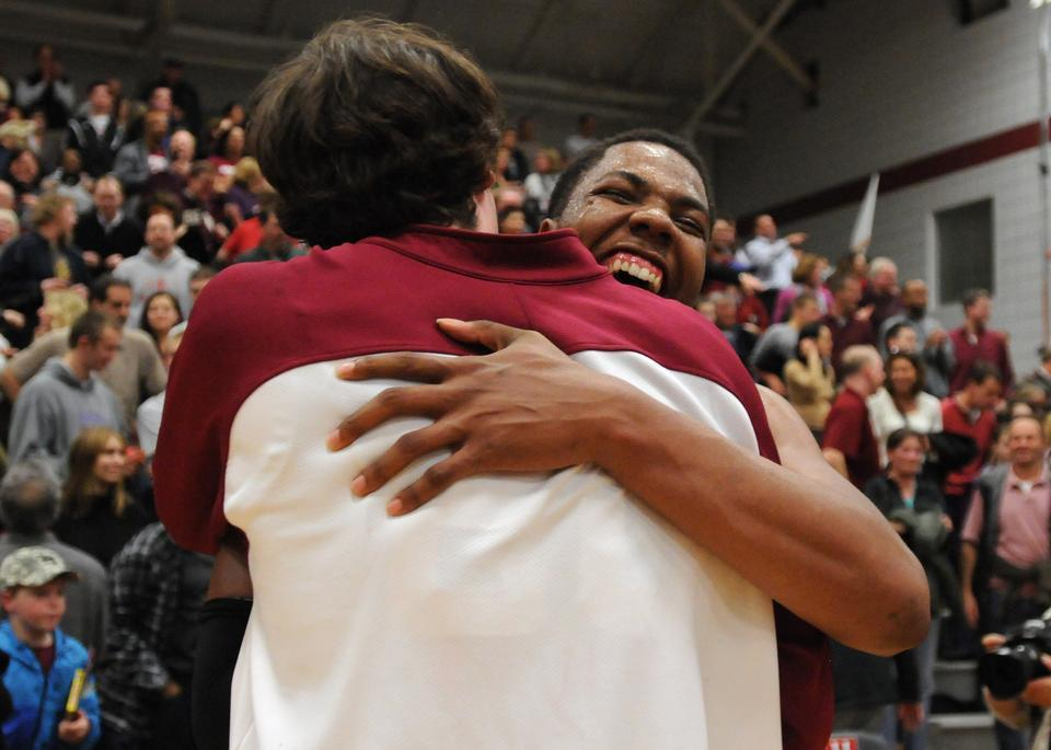Junior co-captain Keith Wright (right) embraces classmate Andrew Van Nest after the two helped Harvard garner a share of its first-ever Ivy championship in its 100th season of basketball.