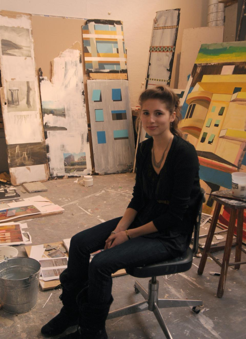 VES concentrator Julia Rooney '11 sits among a small selection of her paintings in her Linden Street studio space.