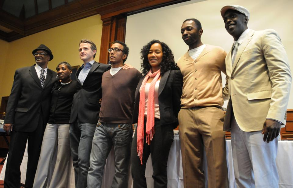 """Donnie Andrews, Fran Boyd Andrews, Jim True-Frost, Andre Royo, Sonja Sohn, Jamie Hector, and Michael K. Williams, all cast members of HBO's acclaimed series """"The Wire,"""" stand before an audience in Ames Courtroom at Harvard Law School."""