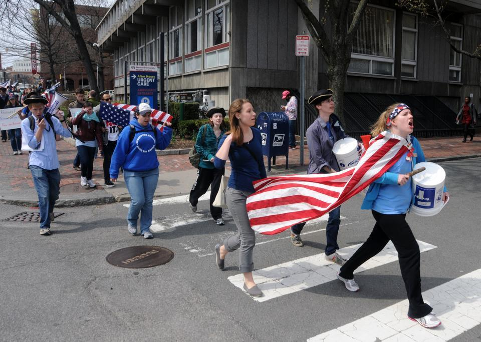 Dozens of protesters participating in the March for Common Sense pass through Harvard Square yesterday as they retrace Paul Revere's ride from Boston to Lexington in reverse.
