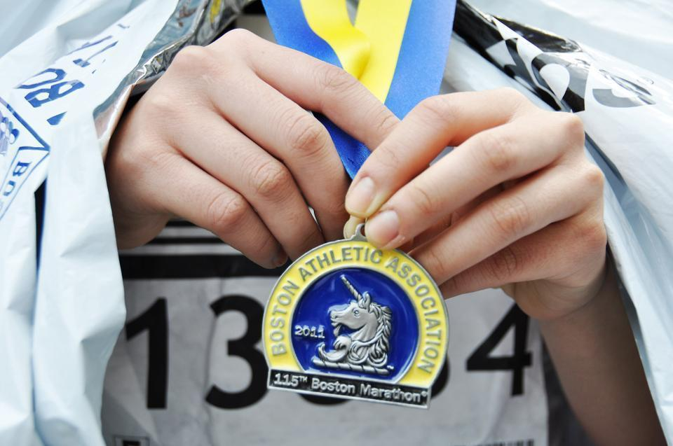 A race-finisher shows off her finisher's medal after completing the grueling 26.2-mile run.