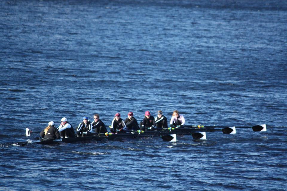 Shown here in earlier action, the Radcliffe heavyweight varsity eight finished three seconds ahead of defending NCAA varsity champion Yale Saturday morning on the Charles River, giving the Black and White its first defeat of the Bulldogs in eight years. Yale took first in each of the other three events.