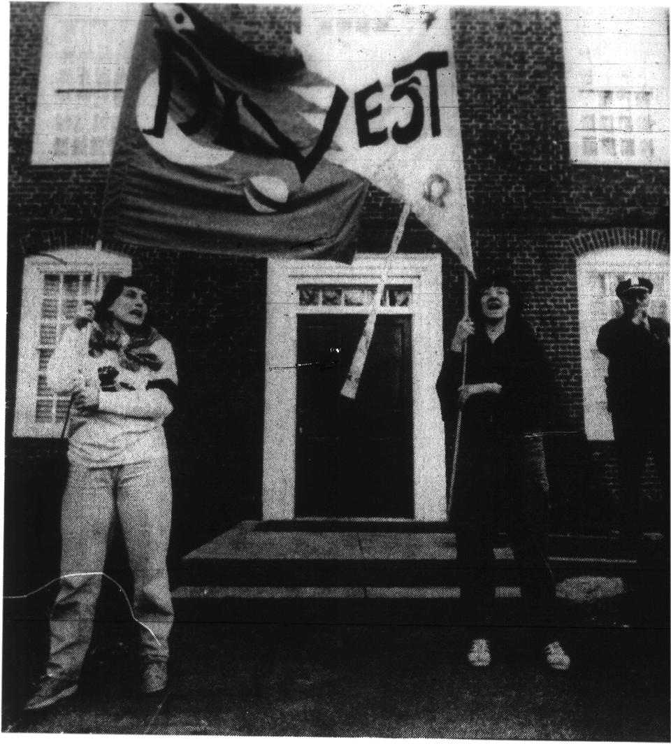 "Student protesters wave a banner in front of Mass Hall in 1986 which reads, ""Divestment."""