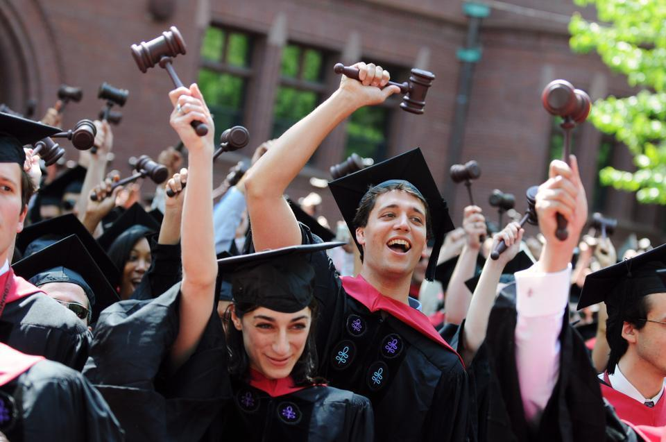 Harvard Law School students celebrate the conferral of their degrees, shaking gavels in the air as symbols of their area of study.