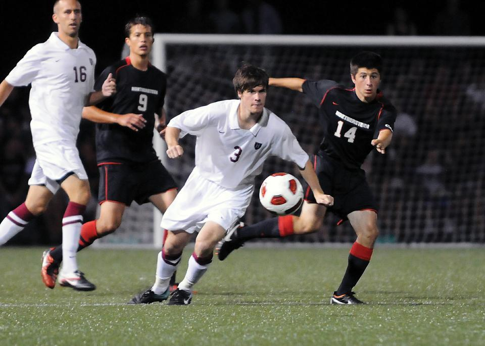 Junior co-captain Scott Prozeller looks to pass the ball in the Crimson's 1-0 victory against Northeastern. Soldiers Field Soccer Stadium was packed with 2,500 fans for the men's soccer team's annual start of the season under the lights. The squad will travel to New York Friday to face St. John's.