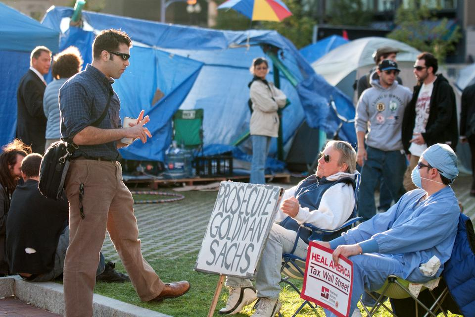 Michael, a retired teacher, and his son Justin, an unemployed surgical technician, discuss and debate the state of the economy and other topics with people at the Occupy Boston protest.