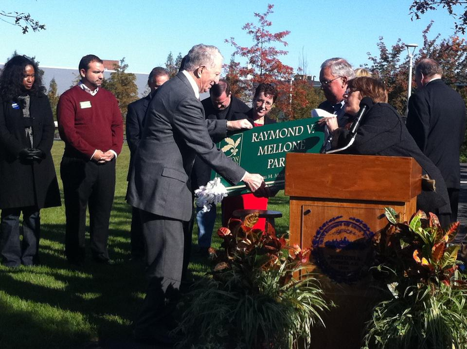 Boston Mayor Thomas M. Menino presents a sign to long-time Allston resident Raymond V. Mellone Saturday morning as the announcement was made that Library Park would be named after Mellone.