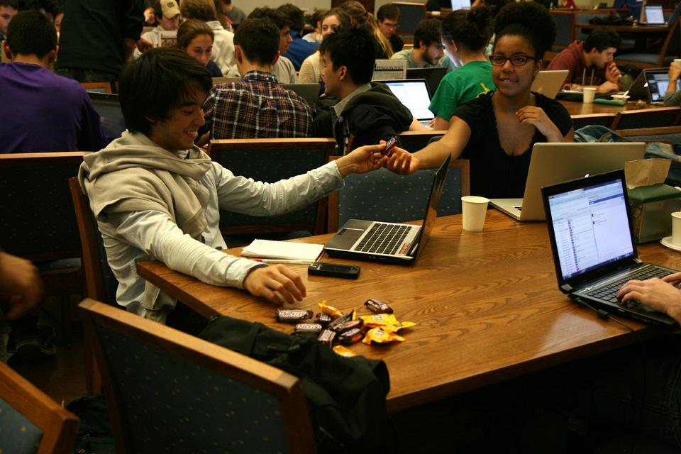 Teaching staff and students gather at Quincy House on Wednesday night for CS50 tables. Students pass around candy bars to help refuel while working on the final problem set of the semester.