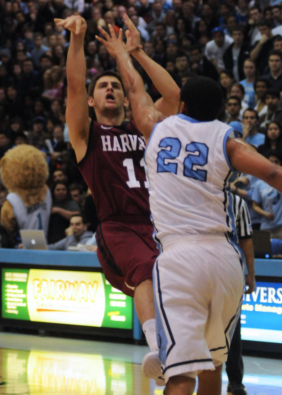 Co-captain Oliver McNally attempts a shot over Columbia's Meiko Lyles during the Crimson's 77-70 overtime win against the Lions on Friday at Levien Gymnasium. McNally finished with 12 points and four assists in 38 minutes of action.