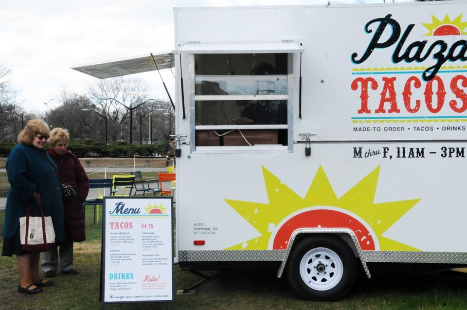 In the space that used to be the skating rink outside of the Science Center, customers look at the menu of Plaza Tacos, a new food truck run by Harvard University Dining Services.