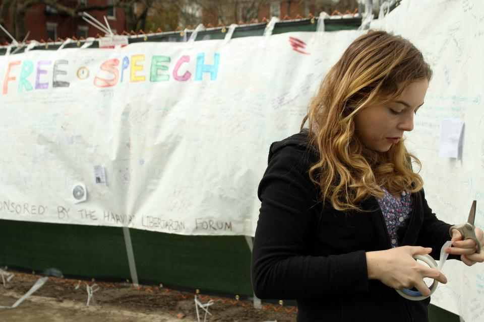 """Corrine H. Curcie '15, a member of the Harvard Libertarian Forum, tapes up a portion of the """"free speech banner"""" on the Science Center Plaza Thursday afternoon. The HLF, which sponsored the banner, hopes to draw attention to Harvard's free speech policies in light of the school's recent inclusion on the Foundation for Individual Rights in Education's annual """"12 Worst Colleges for Free Speech"""" list."""