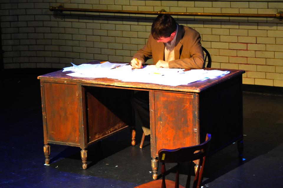 """Sitting at the desk is Peter Bestoso, playing the part of """"The Man"""", in Monstrous Doubles, a student-written play performed at Adam's Pool Theatre."""
