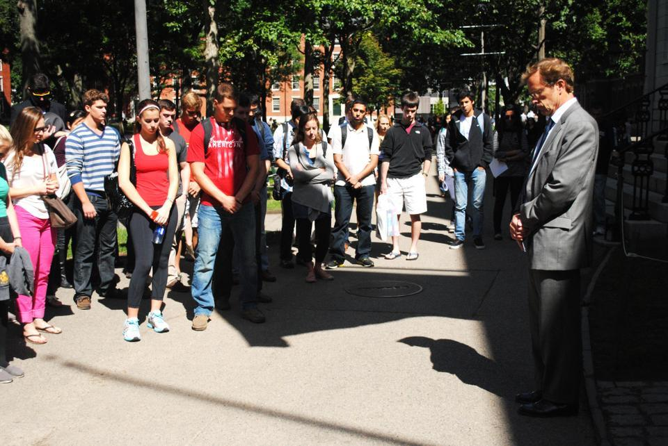 "Dean of Freshmen, Tom Dingman, and students gather in the shadow of John Harvard and the American flag, as they remember the attacks on September 11, 2001 -  ""Let us bow our heads in a moment of silence""."