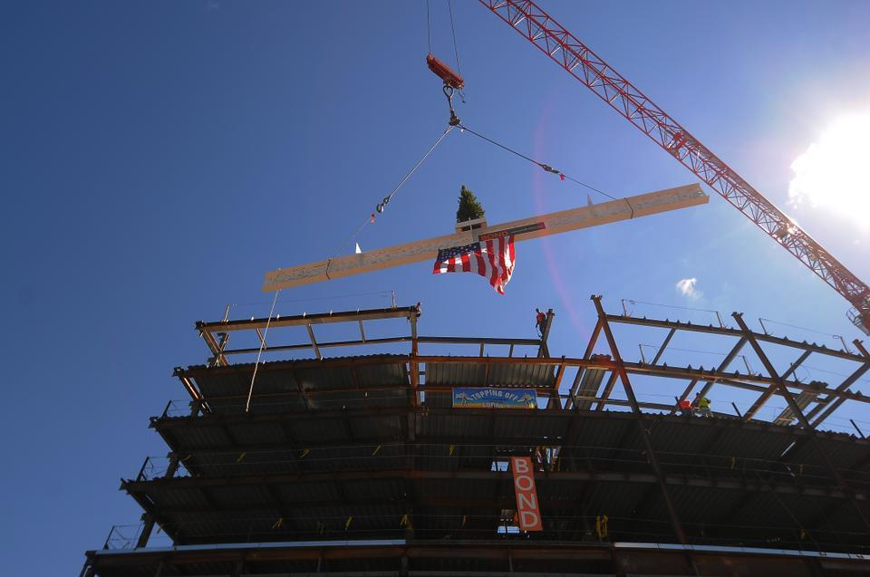 "The highest steel beam of the new Tata building is hoisted above a crowd on the Business School campus on Monday. It was painted white and adorned with dozens of signatures and a small pine tree according to a Norse tradition adopted by steel workers in ""topping off"" ceremonies."