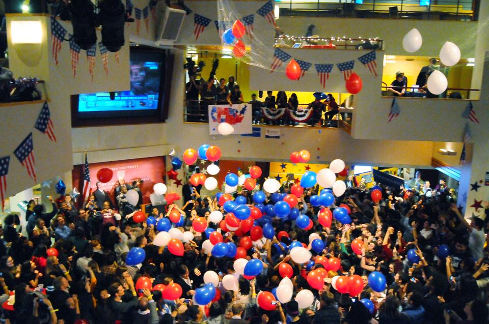 At 12:20AM after CNN released their projection that Obama had won the Presidential election, dozens of balloons drop onto spectators below at the Kennedy School's IOP election watch party.