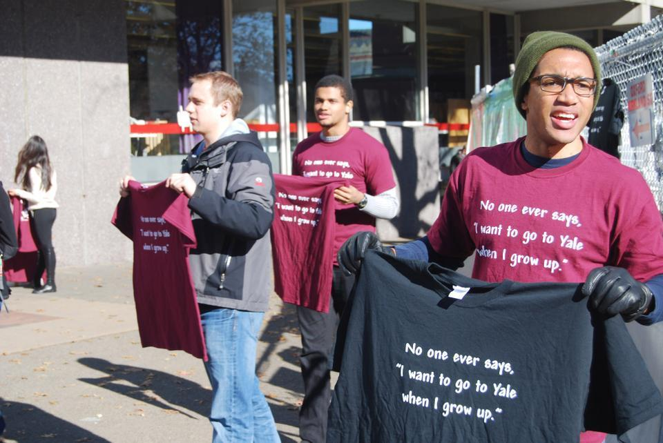 Harvard Seniors, from left to right, Chris H. Weber, Andreas M. Haggerty, and Hilton H. Augustine, sell t-shirts outside the science center Wednesday afternoon for The Game against Yale this coming Saturday.