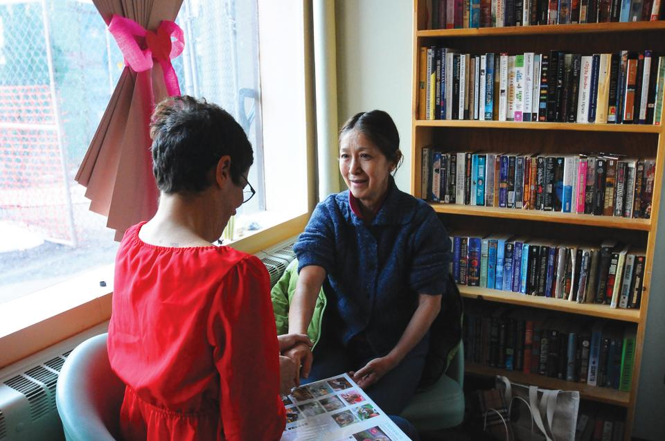 YWCA Tanner House Case Manager, Schuyler S. Engel gives resident, Yoko Hershiki a hand massage. The Valentine's Day event at the YWCA gave homeless women makeovers with the help of cosmetics donations from the Harvard community.