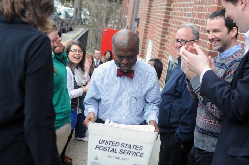 Senior Admissions Officer David L. Evans emerges from the Admissions Office with the first box of acceptance letters for the class of 2017, to be loaded onto a waiting mail truck, on Wednesday as his fellow admissions officers cheer. After an hour-long delay in the arrival of the truck, Admissions Office employees formed an assembly line to send off regular decision acceptance packets and rejection letters.