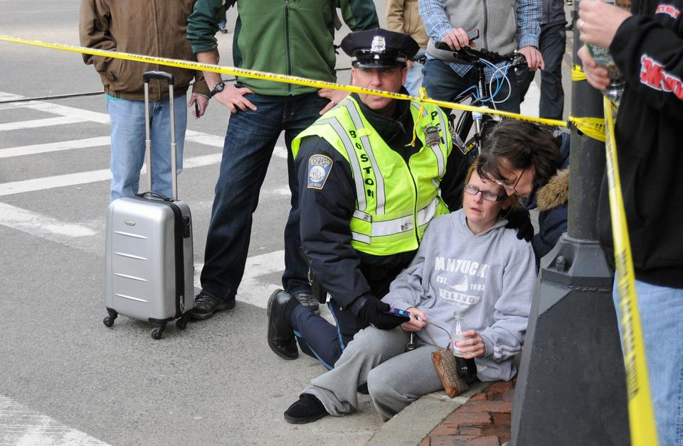 A shocked onlooker of the bombings in Copley Square is comforted by a officer of the Boston Police Department.
