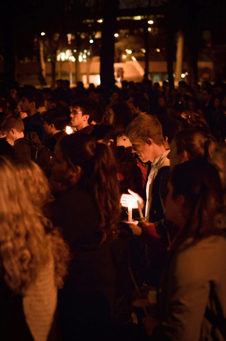 Members of the Harvard community gather outside Memorial Church at a candlelight vigil to commemorate all those who suffer as a result of the Boston Marathon explosion.