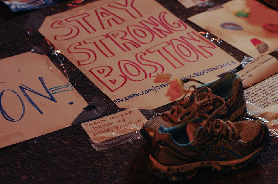 Many people brought signs; flowers; and other tokens to a memorial set up at the barrier on the intersection of Boylston and Berkley Street; just a few blocks beyond the marathon's finish line. These shoes were brought by Lisa Mara, a Bostonian runner who finished fifteen minutes before the blasts. Other items included a marathon medal, candles, and numerous handwritten letters.