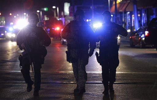 Officers wearing tactical gear arrive in Watertown on Friday, April 19, 2013. Reports of explosives being detonated and police are telling reporters to turn off their cell phones. Dozens of officers and National Guard members are in Watertown, where television outlets report that gunfire and explosions have been heard.