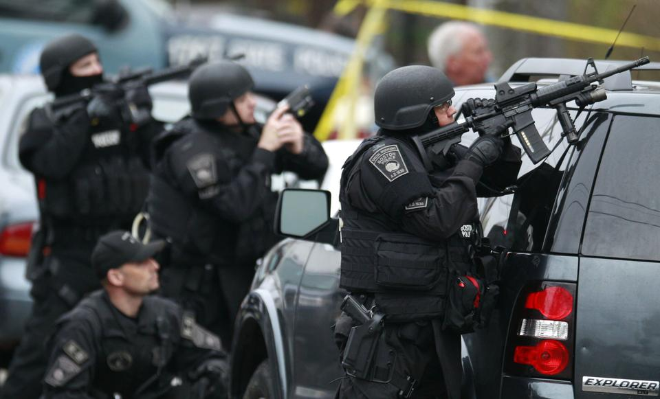 Police in tactical gear surround an apartment building while looking for a suspect in the Boston Marathon bombings in Watertown, Mass., on Friday. All residents of Boston were ordered to stay in their homes Friday morning as the search for the surviving suspect in the marathon bombings continued after a long night of violence that left another suspect dead.