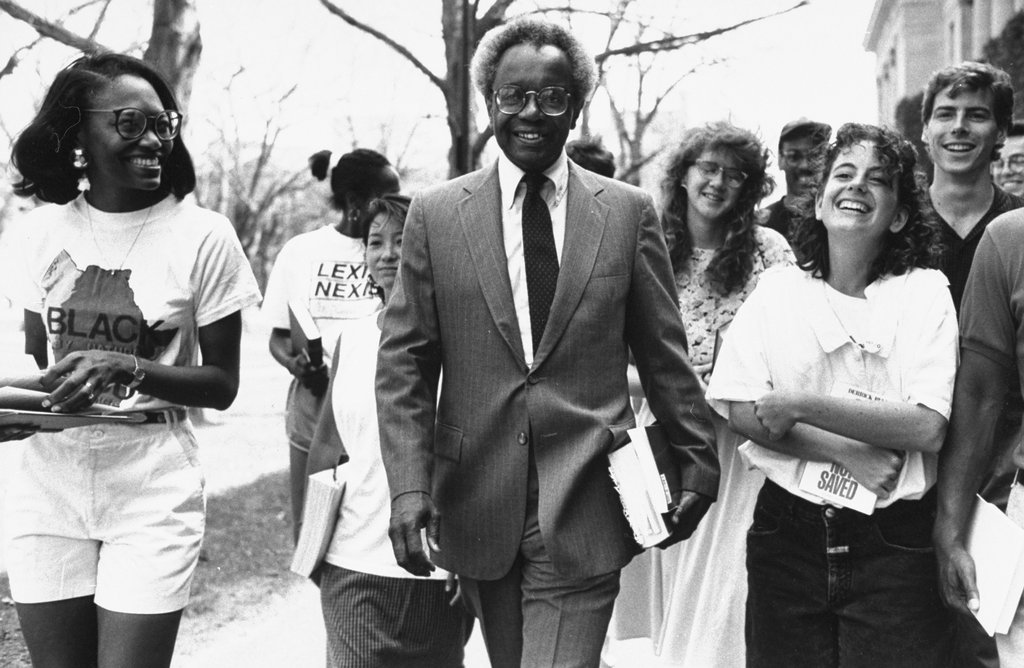 Derrick Bell walks with a group of Harvard Law School students after taking a voluntary unpaid leave of absence to protest the lack of tenured minority female professors.