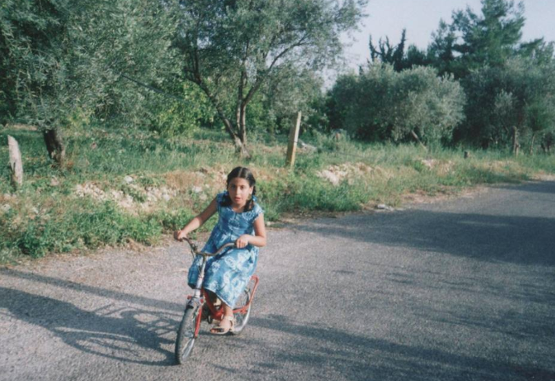 A young Nisreen Shiban rides her bike in Syria.