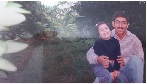 A photo of a young Nisreen Shiban '17 shows her laughing on the lap of her uncle Makarem, a former veterinarian who had practically raised her.