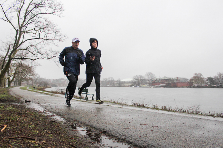 Lawrence S. Bacow and Fifteen Minutes Magazine writer Luke W. Xu '20 run along the Charles River on a rainy Marathon Monday.