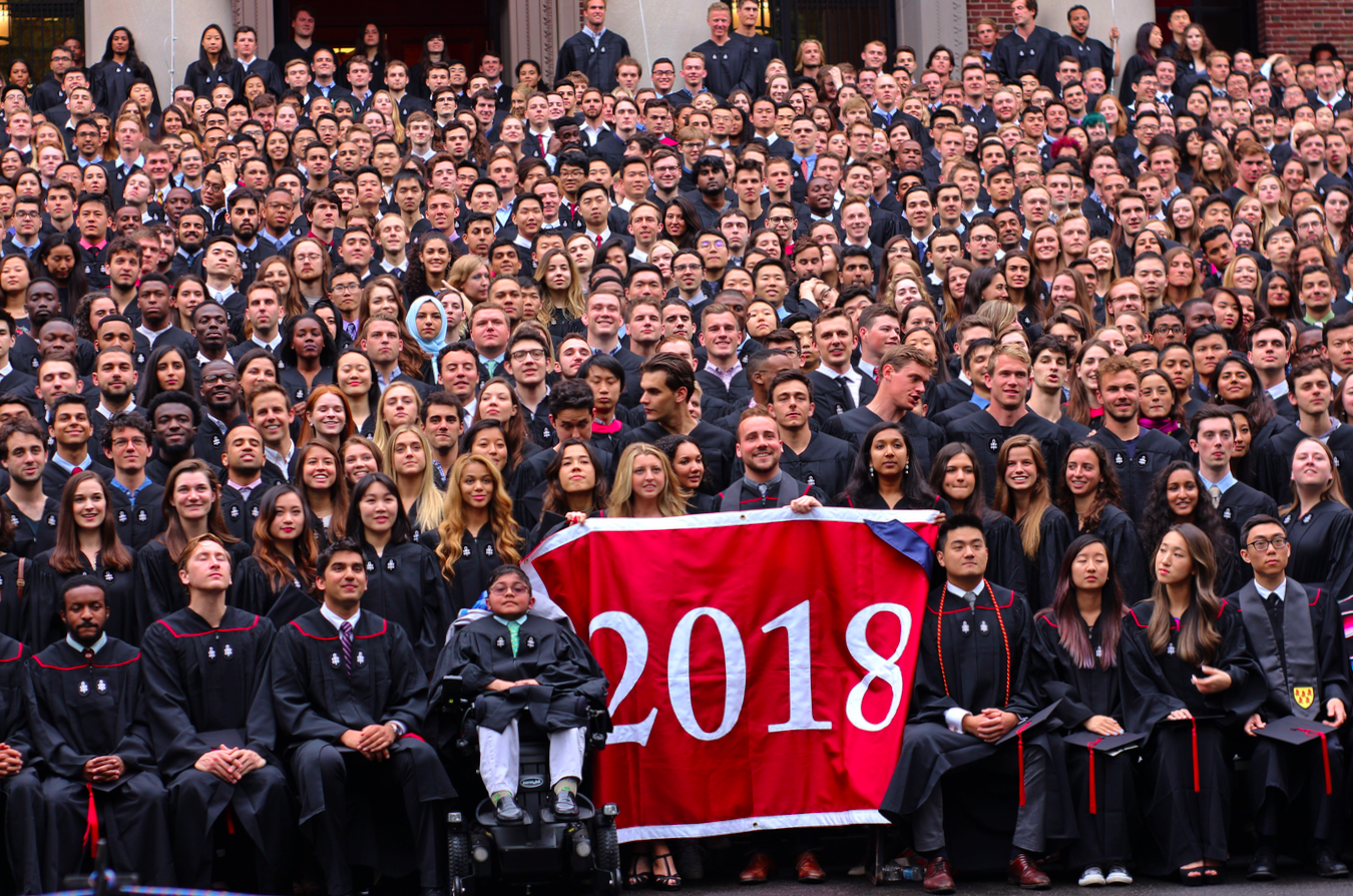 The Class of 2018 pose for a class photo on the steps of Widener library.